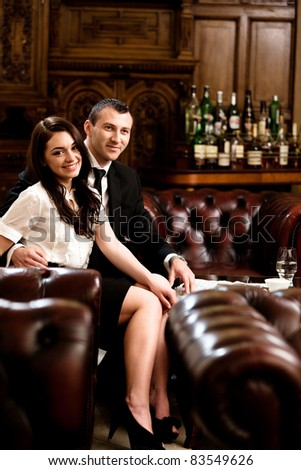 Attractive business couple smiling while is looking on a newspaper. Please see more images from the same shoot. - stock photo