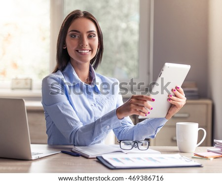 Attractive business lady in formal clothes is using a digital tablet, looking at camera and smiling while working in office