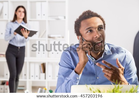 Attractive business man and woman doing paperwork and talking on phone in office. Concept of teamwork. Office interior in the background - stock photo