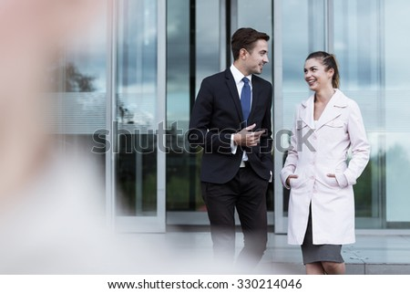 Attractive business man and woman talking after work