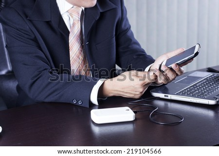 Attractive Business man charging his mobile phone  - stock photo
