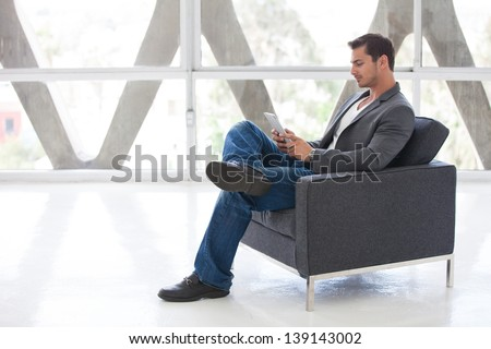 Attractive business man in his 20s working on a think pad - stock photo