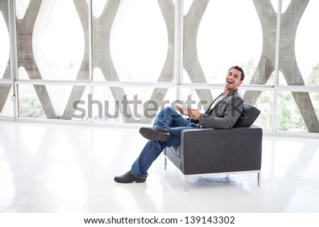 Attractive business man in his 20s working on a think pad in a wide open space - stock photo
