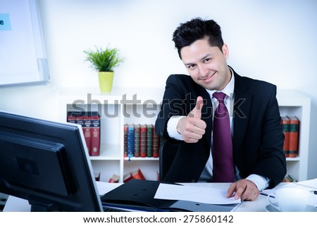 attractive business man in office shows thumb up