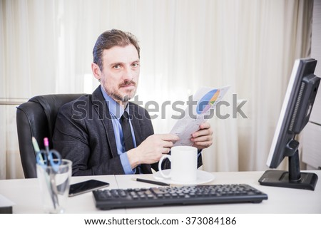 attractive business man is sitting on his desktop - stock photo