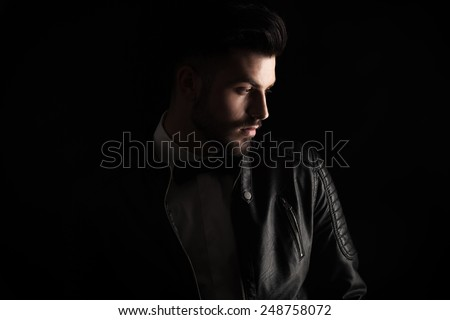 Attractive business man looking down to his side on dark studio background. - stock photo