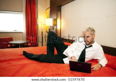 Attractive business man on his laptop in bed - stock photo