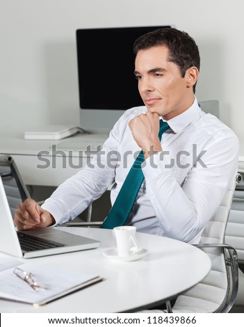 Attractive business manager working with laptop at office desk - stock photo