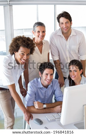 Attractive business people smiling at the camera whilst working on a computer - stock photo