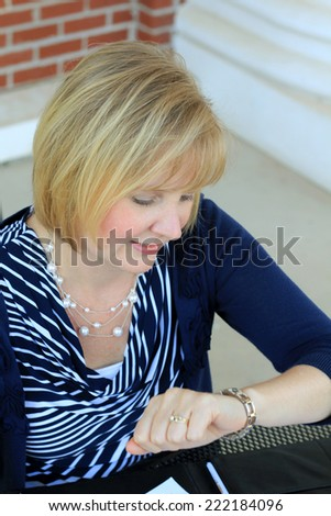 Attractive Business Professional Business Woman Checking Her Watch Time Wearing Blue Shirt