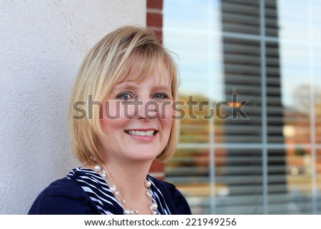 Attractive Business Professional Business Woman Smiling and Happy Baby Boomer Mom Friendly - stock photo
