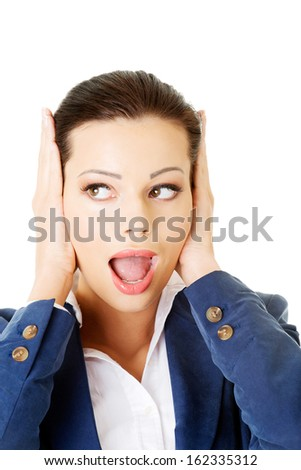 Attractive business woman covers her ears. Isolated on white.  - stock photo