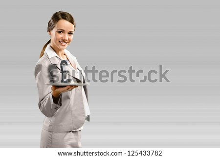 attractive business woman holding a tablet with british pound, place for text - stock photo