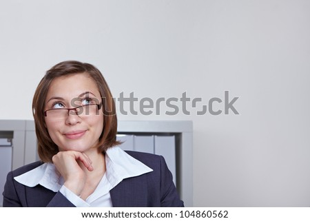 Attractive business woman in office looking pensively up - stock photo