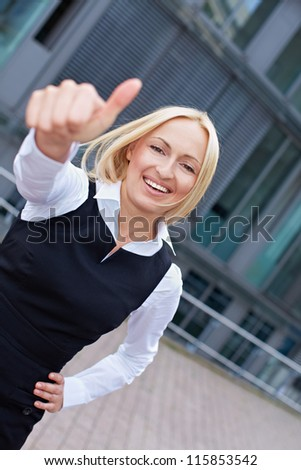 Attractive business woman in the city holding her thumbs up - stock photo