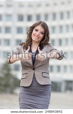 Attractive business woman in town. Urban young woman showing thumbs up - stock photo