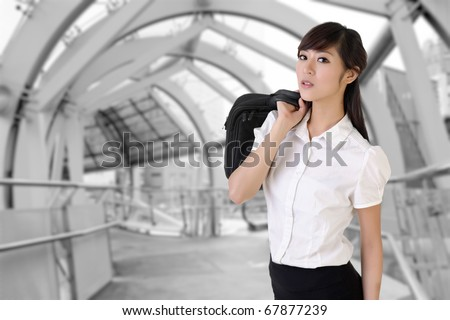 Attractive business woman of Asian holding briefcase inside of modern architecture of flyover. - stock photo