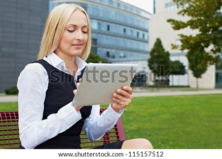 Attractive business woman outside holding a tablet PC - stock photo