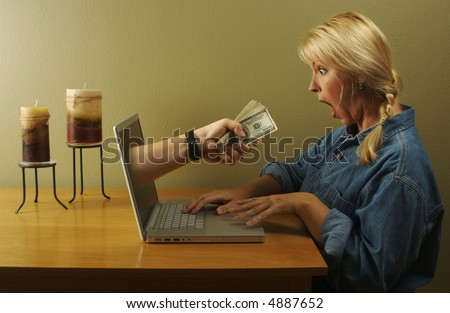 Attractive business woman shocked to see a hand coming through her laptop screen handing her lots of money. Can it be that simple? - stock photo