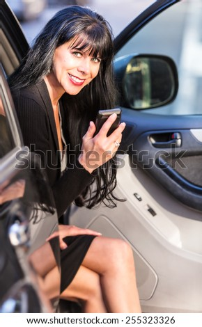 Attractive business woman with smart phone sitting in automobile - stock photo