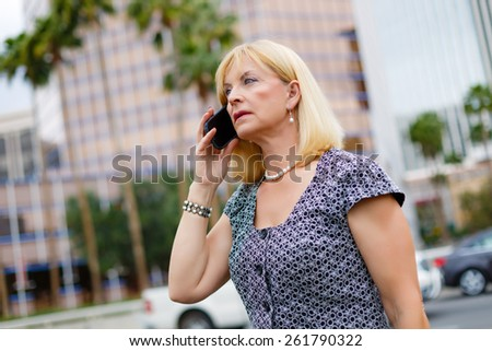 Attractive business woman 65 years in the downtown calling with mobile phone, Lifestyle woman on phone, Business concept - businesswoman talking on the phone in street - stock photo