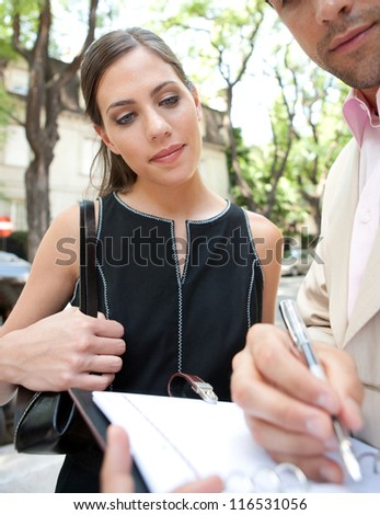Attractive businessman and businesswoman meeting in a classic city street and looking at notes, exterior. - stock photo