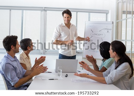 Attractive businessman being applauded for his amazing presentation. - stock photo