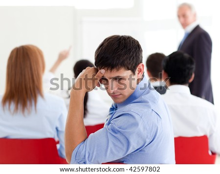 Attractive businessman bored at a conference with his colleagues - stock photo