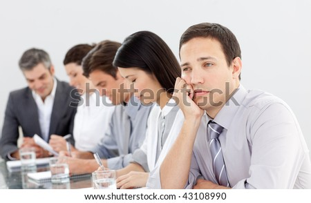 Attractive businessman bored at a presentation with his team - stock photo