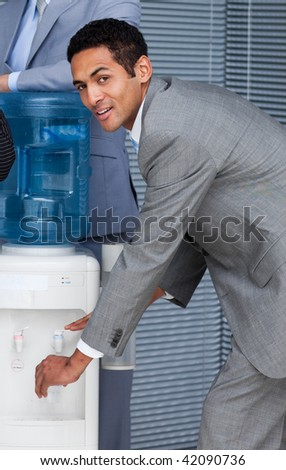 Attractive businessman filling cup from water cooler in the office - stock photo