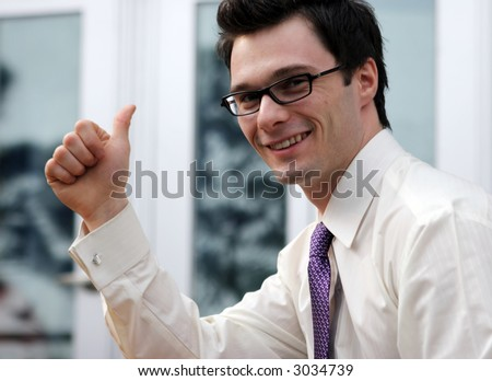 Attractive businessman gives the thumbs up gesture. - stock photo