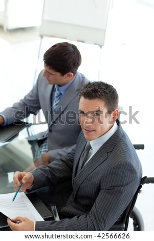 Attractive businessman in a wheelchair pointing a document - stock photo