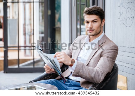 Attractive businessman in suit is sitting at table in cafe outdoors