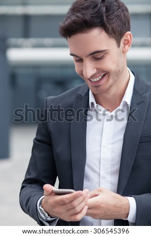 Attractive businessman is holding a mobile phone and messaging to his colleague. He is looking at the technology with joy and smiling. The worker is standing near his office - stock photo