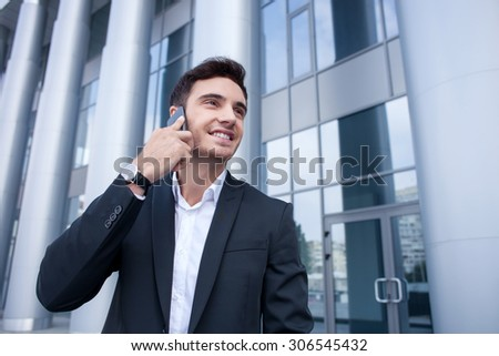 Attractive businessman is talking on the phone and standing near his office. He is smiling and looking forward with joy. Copy space in right side