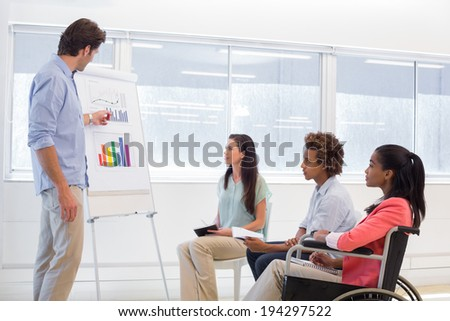 Attractive businessman making a presentation to his fellow coworkers in the office - stock photo