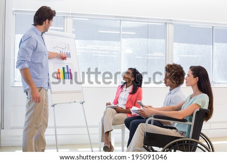 Attractive businessman presenting a graph to his coworkers in the office - stock photo