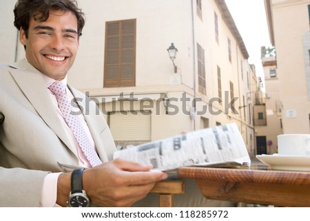 Attractive businessman reading the newspaper in a coffee shop terrace table in a classic city, smiling at the camera, outdoors. - stock photo