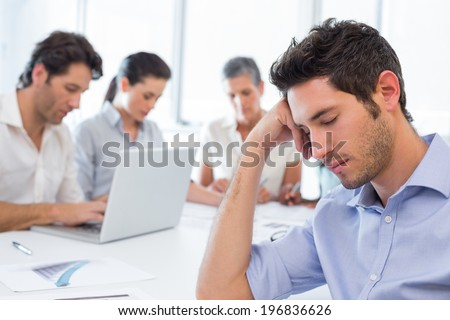Attractive businessman resting upon the table in the office whilst his coworkers are working in the background - stock photo