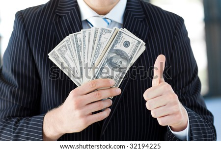 Attractive businessman showing dollars with thumbs up - stock photo