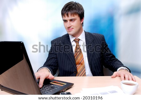 Attractive businessman sitting at the desk and working on a laptop