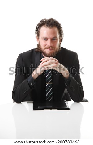 Attractive businessman sitting by a table with a clipboard in front of him. White background. - stock photo
