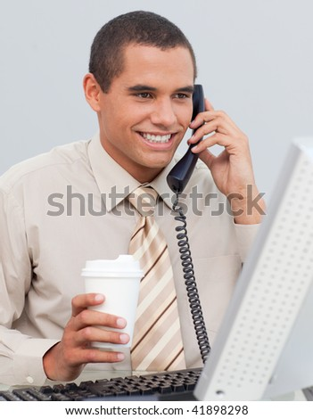 Attractive businessman talking on phone in the office