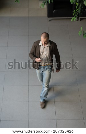 Attractive businessman using his cell phone in office building lobby. Top view - stock photo