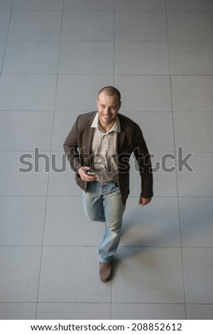 Attractive businessman using his smartphone in office building lobby. Top view - stock photo