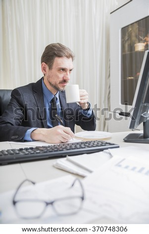 attractive businessman working at business district office sitting at computer desk drinking coffee