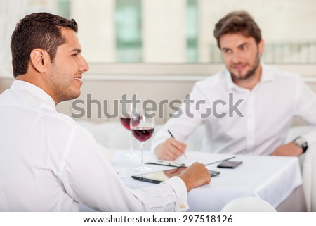 Attractive businessmen have a meeting in cafe. They are sitting at the table and discussing their cooperation. They are smiling and drinking red wine - stock photo