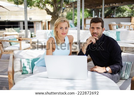 Attractive businesswoman and her colleague smiling looking to the camera sitting an the table in beautiful lounge bar terrace, businesspeople at meeting outdoors, young couple using laptop computer pc