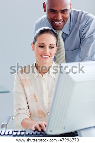 Attractive businesswoman and her manager working at a computer in the office