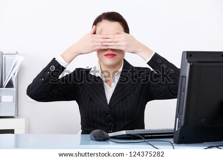 Attractive businesswoman at office covering her eyes. - stock photo